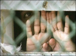 A detainee peering out of a cell at Guantanmo Bay.  (2006 Photo by Brennan Linsley -- Associated Press)