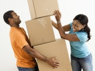 African American female placing boxes on large stack man is holding.